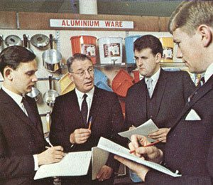 A group of young trainee managers - every one male - receive instruction from a training officer at Woolworth's Castleton in 1969