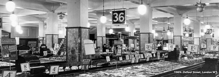A typical salesfloor layout at Woolworth's shortly after World War II. The image shows Store 463 at 150-154 Oxford Street, London, near the British Museum in 1946.  The highest price on display at the time was four shillings and four pence, nearly nine times the pre-war maximum.
