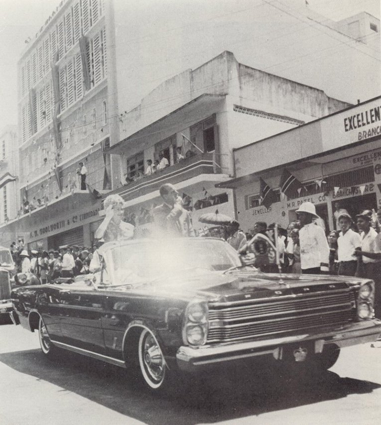 Her Majesty Queen Elizabeth II and His Royal Highness Prince Philip drive past Woolworths on a state visit to Trinidad and Tobago in the 1960s