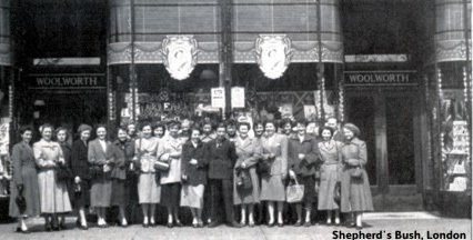 Colleagues from Woolworths at Shepherd's Bush preparing to celebrate H. M. The Queen's Coronation. In the background the store front is decorated with flags, bunting and pictures of the Queen.