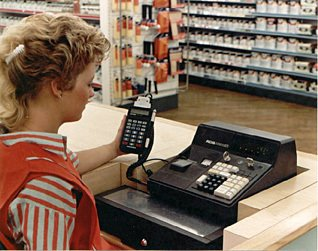 A colleague uses a Telxon PTC-701 Hand-held terminal to extract departmental sales and items sold data from an Anker Data Systems ADS till in a Woolworths store in 1987.