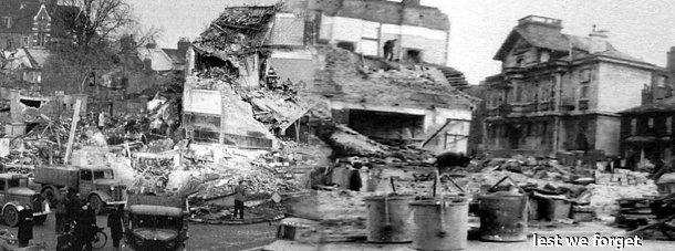 "The devastation following the New Cross explosion.  Remember the heroes who dug with their bare hands in search for survivors.   (Note that the ornate Deptford Town Hall, which is still standing today, (and is now part of Goldsmiths College, University of London,) is clearly visible to the right of the picture above the words ""lest we forget"".   Click for greater detail in a new window."