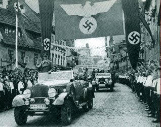 "Adolf Hitler makes a ""triumphal"" entry into Asch, in the process liberating Fleissen from 290 years of tolerance and freedom, for the ""safety and security"" of oppression and fear."