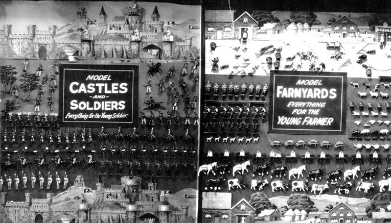 A toys window from Christmas 1937, featuring castle and lead soldiers on the left and another range from Britain's on the right - a selection of farmyard animals made from lead