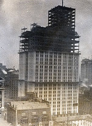 The spire of the Woolworth Building rises from the streets of Manhattan as building work continues